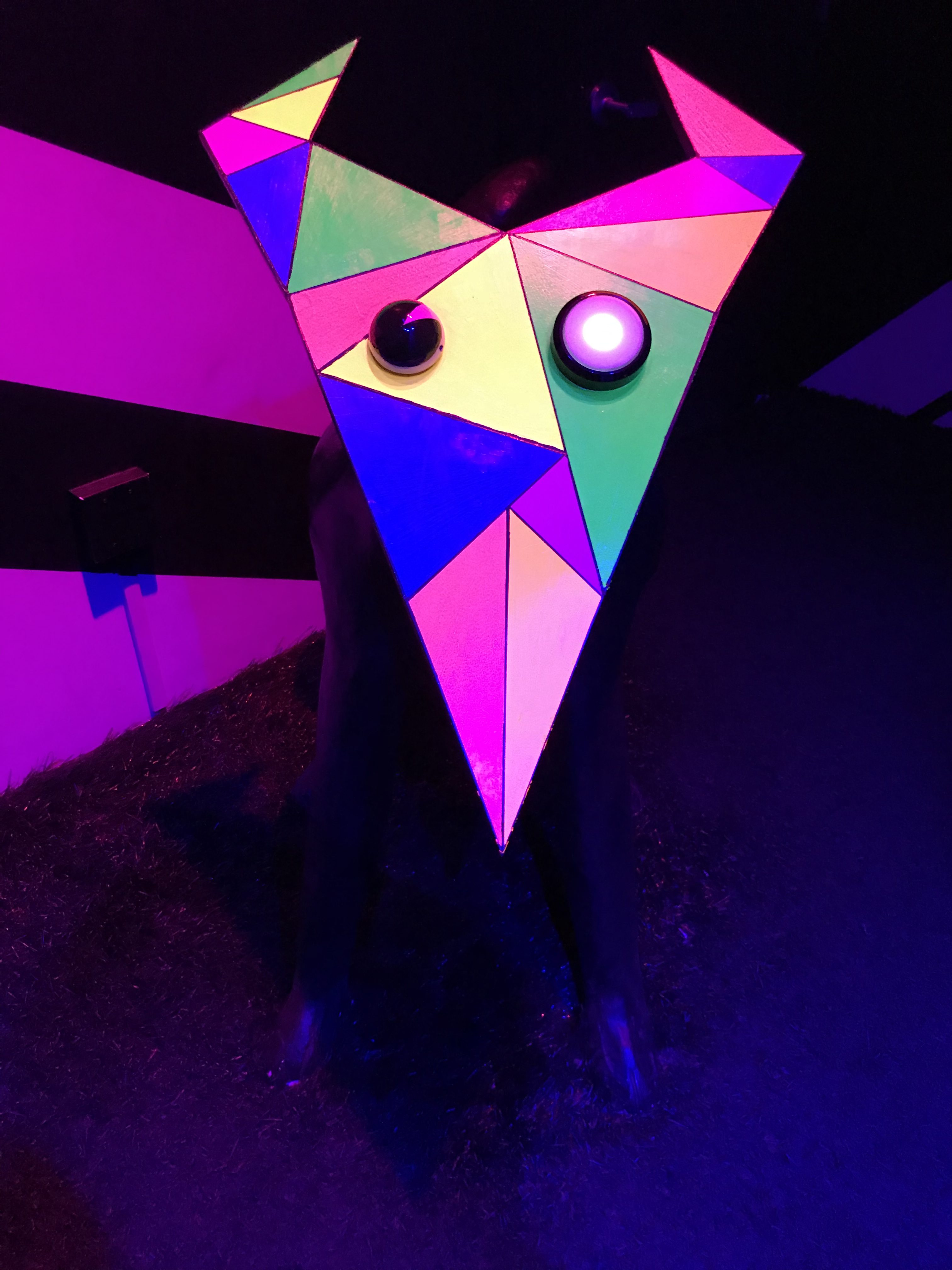 sculpture from Meow Wolf - doglike creature with triangular face and prismatic rainbow coloration